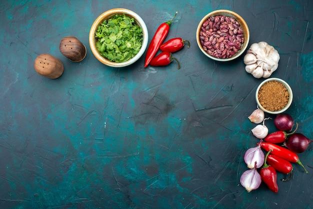 Вид сверху красный перец чили с зеленью, луком, чесноком на темно-синем фоне, еда, еда, овощи