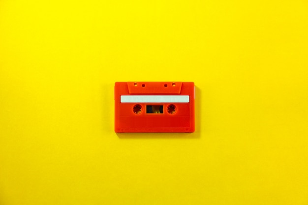 Top view of red classic tape cassette against yellow isolated background