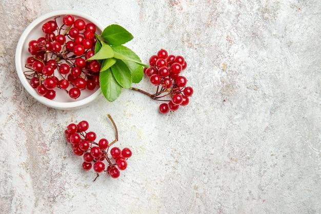 Вид сверху красная клюква свежие фрукты на белом столе свежие ягоды красные фрукты
