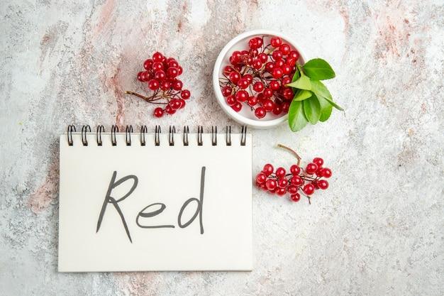 Mirtilli rossi di vista superiore con il blocchetto per appunti scritto rosso sulla frutta rossa della bacca fresca della tavola bianca