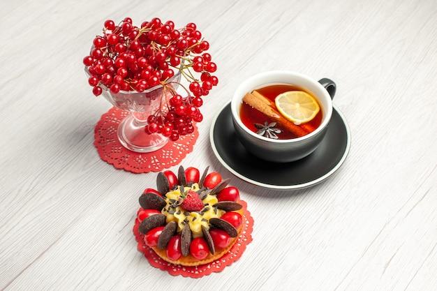Vista dall'alto ribes rosso in un bicchiere di cristallo sul centrino di pizzo ovale rosso una tazza di tè al limone e cannella e torta ai frutti di bosco sul tavolo di legno bianco