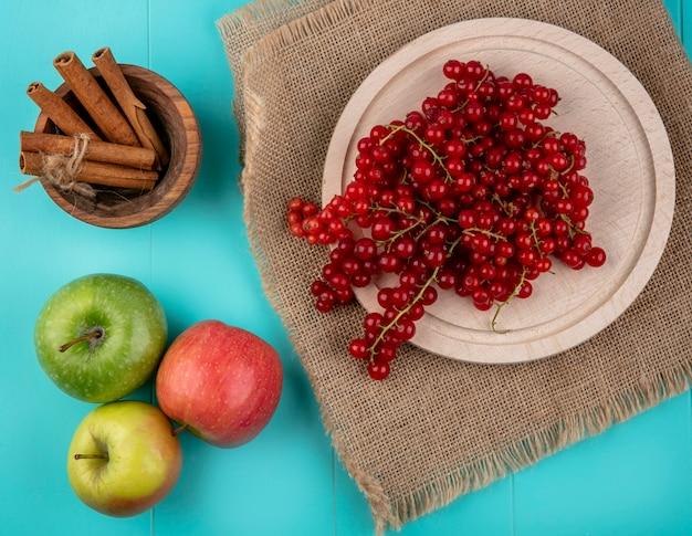 Вид сверху красная смородина на тарелку с яблоками и корицей на голубом фоне