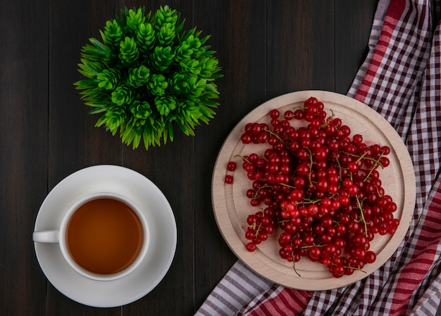 Top view red currant on a plate on a kitchen towel with a cup of tea on a wooden background