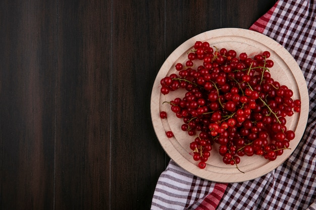 Top view red currant on a plate on a kitchen towel on a wooden background