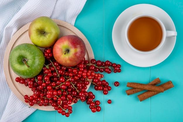Вид сверху красная смородина с яблоками на тарелке с корицей и чашкой чая на голубом фоне