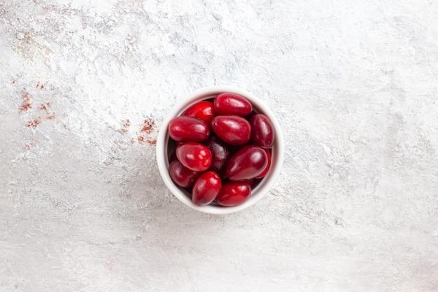 Vista dall'alto cornioli rossi all'interno del piccolo piatto sulla pianta dell'albero di colore della frutta a bacca di superficie bianca