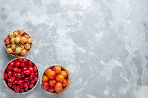 Вид сверху красных кизилов с алырями и вишнями на светлом столе
