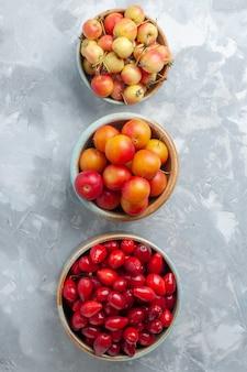 Вид сверху красных кизилов со сливой и вишней на белом столе