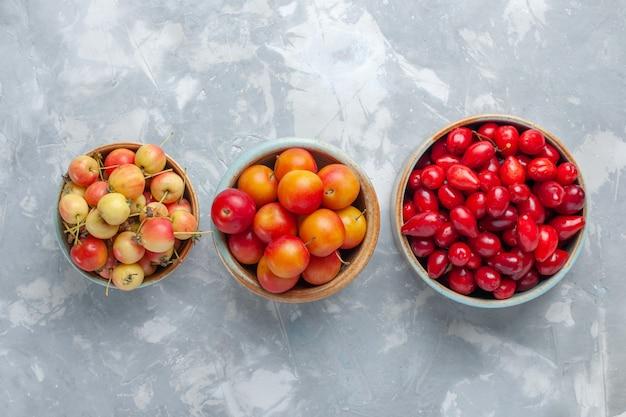 Vista dall'alto cornioli rossi con prugne e ciliegie sulla scrivania bianca
