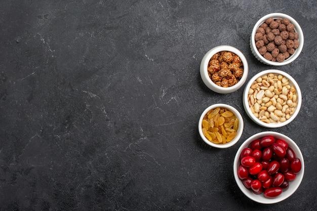 Вид сверху красных кизилов с орехами и изюмом на сером фоне конфеты, сахар, фрукты, сладкий орех
