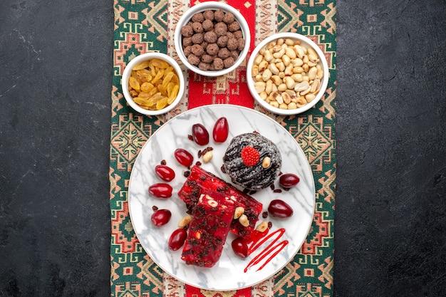 Vista dall'alto cornioli rossi con noci e fette di torrone su uno sfondo grigio zucchero candito frutta noci dolci