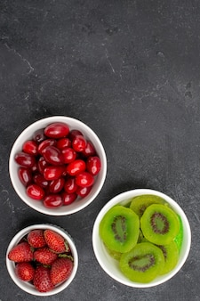 Вид сверху красных кизилов с клубникой и киви на сером фоне фруктовый свежий экзотический спелый