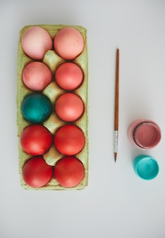 Top view of red easter eggs in crate with red accent arranged in minimal composition on white background, copy space