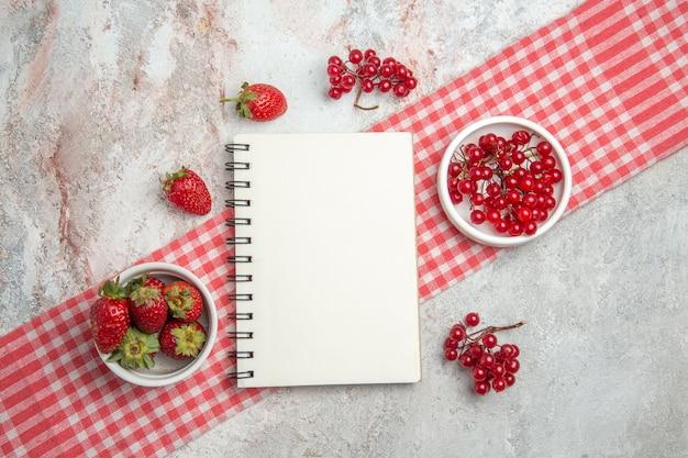 Вид сверху красные фрукты с ягодами на белом столе, блокнот со свежими фруктами и ягодами