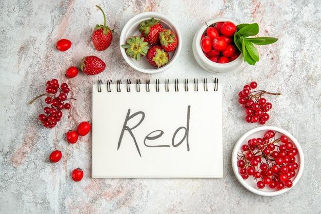 Frutti rossi di vista superiore con il blocco note scritto rosso sui frutti rossi della bacca della tavola bianca