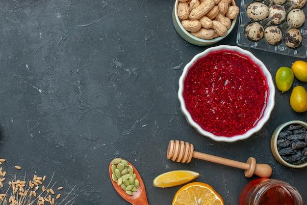 Gelatina fruttata rossa vista dall'alto con arachidi e uvetta sul biscotto di torta di pasta di noci color marmellata grigio scuro