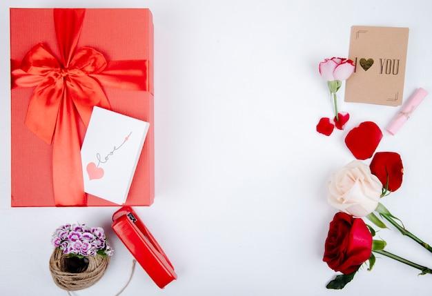 Vista superiore del contenitore di regalo rosso con un arco e rose rosse e bianche di colore con la cucitrice meccanica e la piccola cartolina su fondo bianco con lo spazio della copia