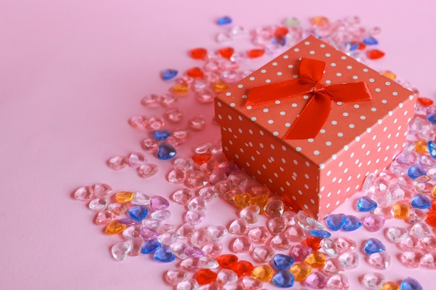 Top view of red gift box with heart shaped marbles on pink background