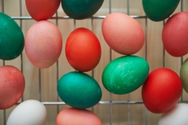 Top view of red and green hand-painted easter eggs on drying rack, copy space