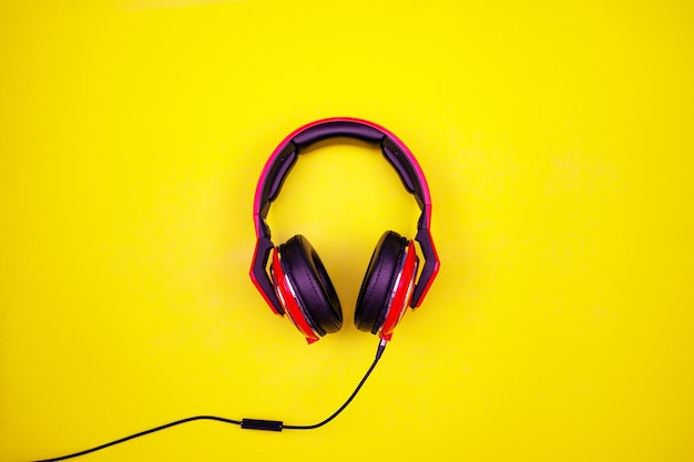Top view of red headphone on light yellow paper background flat lay minimal top down flat lay wireless headphones object studio shot.