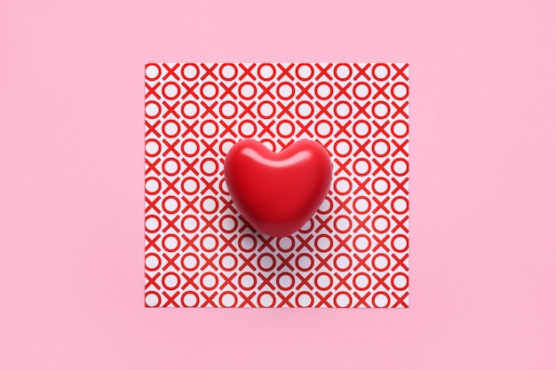 Top view of red heart on background with noughts and crosses in center of pink background.