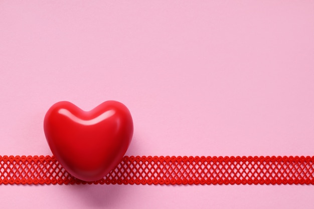 Top view of red heart on horizontal ribbon on pink background, copy space. valentine's day background.