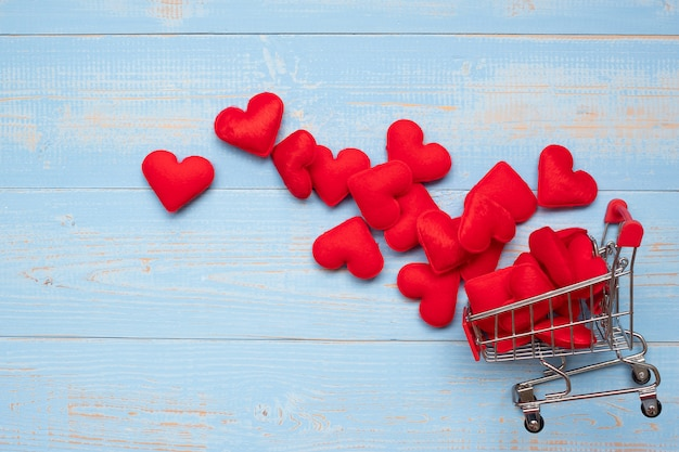 Top view red heart shape decoration with mini shopping cart on blue wooden table background.