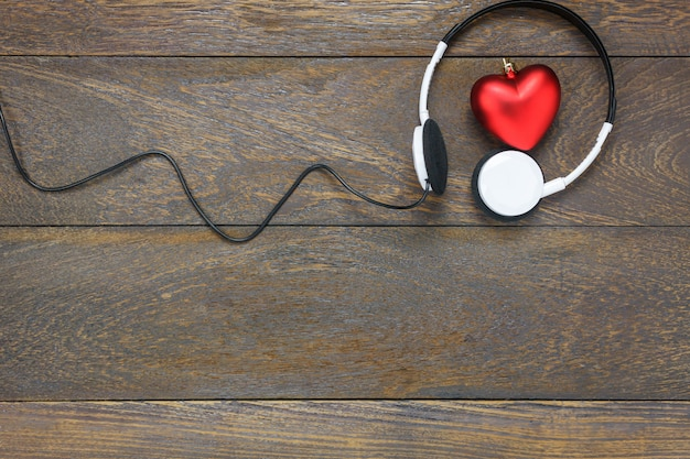 Top view red heart shape listening music with headphones on wooden background and copy space.
