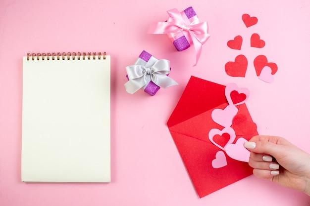 Вид сверху красное сердце наклейки конверт подарки блокнот розовое сердце в женской руке на розовом фоне