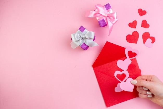 Вид сверху красное сердце наклейки конверт розовое сердце в женской руке подарки на розовом фоне со свободным пространством