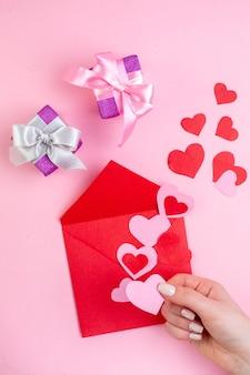 Вид сверху красное сердце наклейки конверт розовое сердце в женской руке подарки на розовом фоне