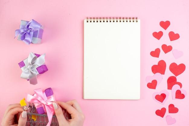 Вид сверху стикеры красного сердца подарок в маленькой рыночной тележке в женской руке ноутбук на розовом фоне