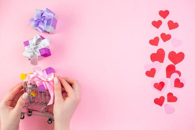 Вид сверху наклейки с красным сердцем в маленькой рыночной тележке в женской руке на розовом фоне