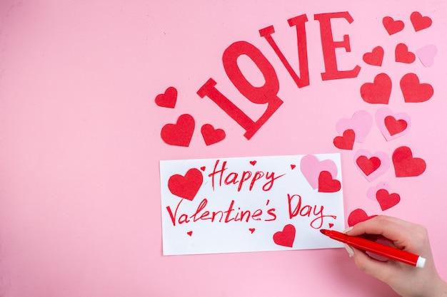 Вид сверху красные сердечные наклейки с днем святого валентина написано на бумаге маркером любовных писем в женской руке на розовом фоне