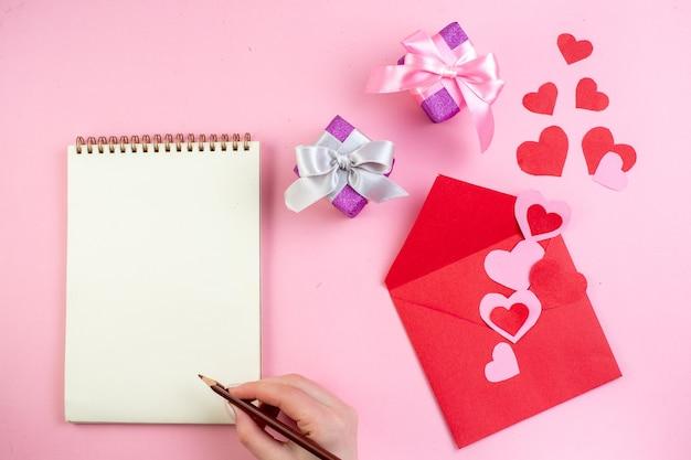 Вид сверху красные сердечные наклейки красный конверт блокнот карандаш в женской руке на розовом фоне