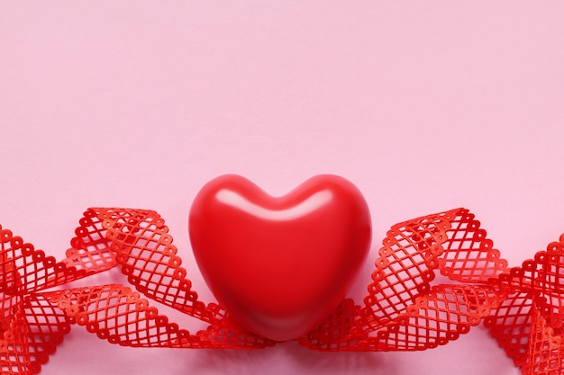 Top view of red heart and twisted ribbon on pink background, copy space. valentine's day background.