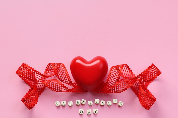 Top view of red heart, twisted ribbon and wooden blocks on pink background, copy space. valentine's day background with wooden letter blocks.