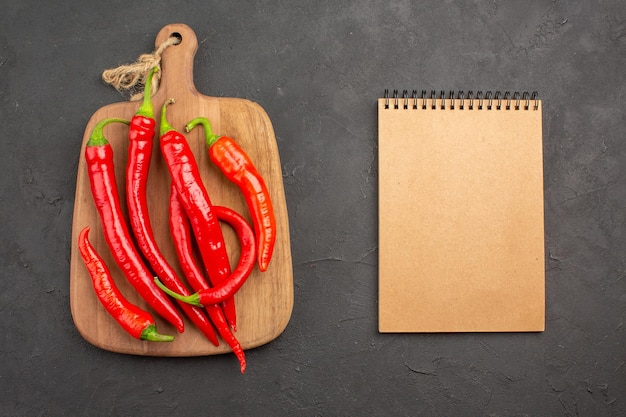 まな板の上の赤唐辛子とコピースペースのある黒いテーブルの上のノートの上面図