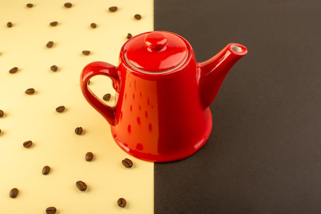 A top view red kettle with brown coffee seeds on the yellow-dark table