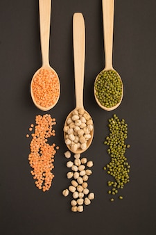 Top view on red lentils, chickpea and mash in the wooden spoons on the dark surface. location vertical.