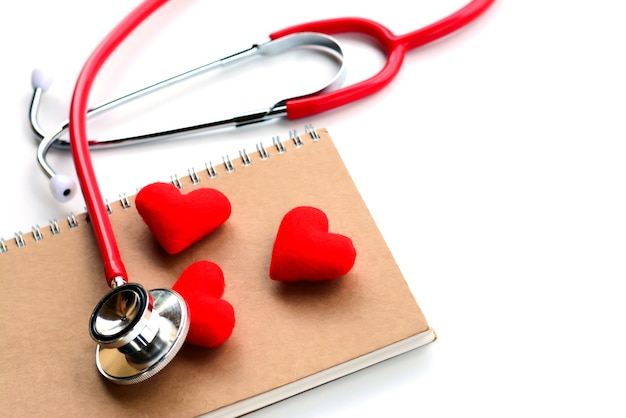 Top view of red medical stethoscope, notebook and red hearts on white background.