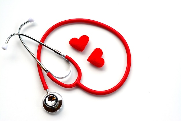 Top view of red medical stethoscope and red hearts on white background.