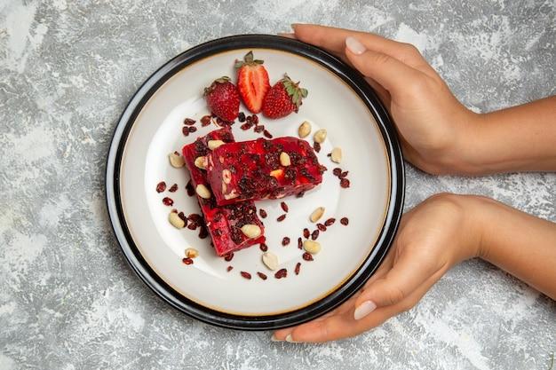 上面図白い表面にナッツと新鮮な赤いイチゴでスライスされた赤いヌガー