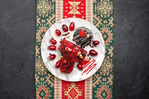 회색 배경 누가 파이 케이크 과일 사탕 쿠키에 초콜릿 케이크와 함께 상위 뷰 빨간 누가 조각