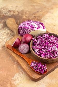 テキスト用のスペースと木製の背景で健康的なサラダの準備を待っている木製のまな板の上のビュー赤玉ねぎとキャベツ