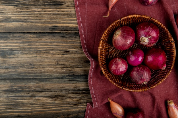 Top view of red onions in basket with shallots on bordo cloth and wooden background with copy space