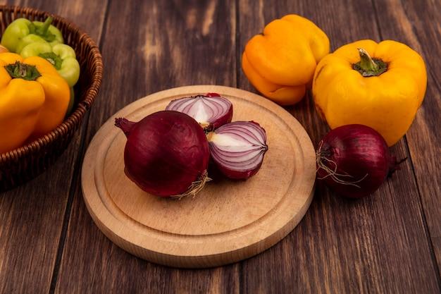 Vista dall'alto di cipolle rosse su una tavola di cucina in legno con peperoni su un secchio con peperoni gialli isolato su una parete in legno