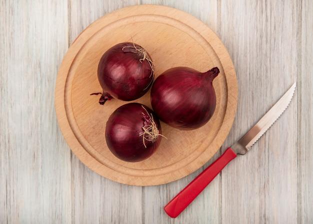 Vista dall'alto di cipolle rosse su una tavola da cucina in legno con coltello su una parete di legno grigia