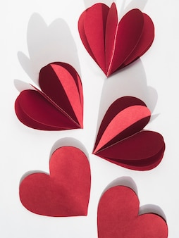 Top view red paper heart shapes on table