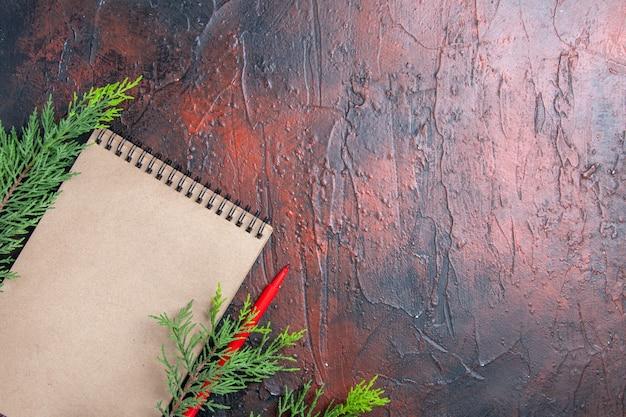 Вид сверху красная ручка блокнот сосновые ветки на темно-красной поверхности свободное место